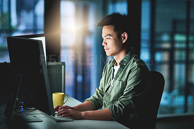 Buy stock photo Cropped shot of a handsome young male designer working late at night on a computer in the office