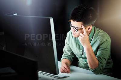 Buy stock photo Cropped shot of a handsome young male designer looking stressed while working late at night in his office
