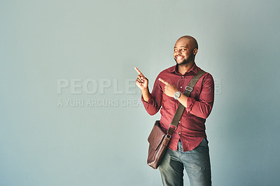 Buy stock photo Studio shot of a handsome young man pointing at something against a grey background