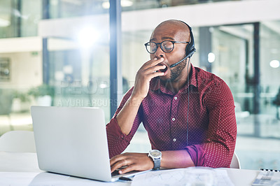 Buy stock photo Shot of a call centre agent yawning while working on his laptop