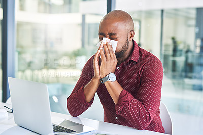 Buy stock photo Shot of a young designer blowing his nose while working in an office