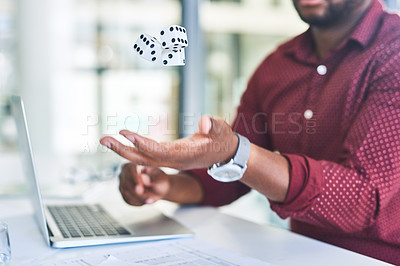 Buy stock photo Cropped shot of an unrecognizable man tossing dice into the air while sitting at his desk