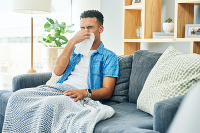 Buy stock photo Shot of a a stressed out young man seated on a sofa while blowing his nose with a tissue due to being sick