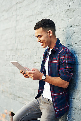 Buy stock photo Shot of a cheerful young man leaning against a wall while browsing on a digital laptop during the day
