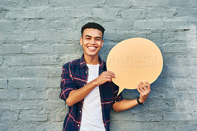 Buy stock photo Portrait of a cheerful young man holding a speech bubble while standing against a brick wall