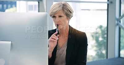 Buy stock photo Shot of a mature businesswoman working on a computer in an office