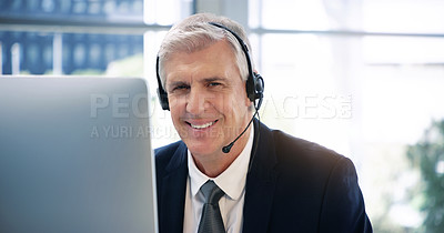 Buy stock photo Portrait of a mature businessman wearing headphones while working on a computer in an office