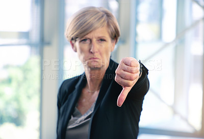 Buy stock photo Portrait of a mature businesswoman showing thumbs down in an office