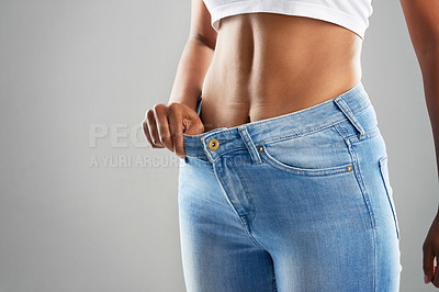 Buy stock photo Cropped studio shot of an unrecognizable young woman in jeans against a gray background