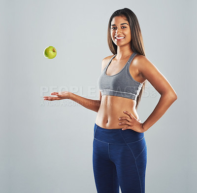 Buy stock photo Cropped studio portrait of a happy young woman throwing an apple against a gray background