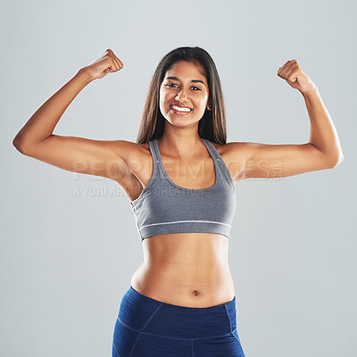 Buy stock photo Cropped studio portrait of an attractive young woman flexing her biceps against a gray background