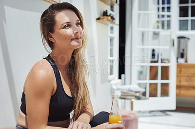 Buy stock photo Shot of a cheerful young woman having a glass of juice while being seated after a yoga workout session