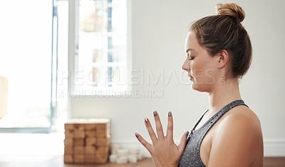 Buy stock photo Shot of a focused young woman doing a yoga pose during a session inside of a studio
