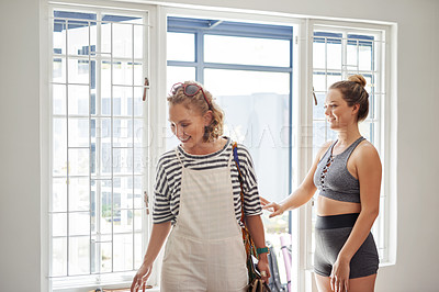 Buy stock photo Shot of a cheerful young woman welcoming her friend to a yoga class inside of a studio