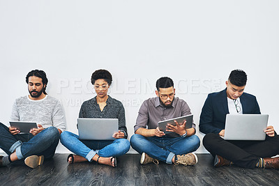 Buy stock photo Studio shot of a group of businesspeople using digital devices against a white background