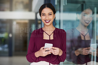 Buy stock photo Portrait of a confident young businesswoman using a smartphone in a modern office