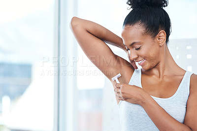 Buy stock photo Shot of an attractive young woman shaving her underarms with a razor in the bathroom