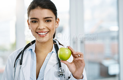 Buy stock photo Portrait of a young female doctor holding an apple