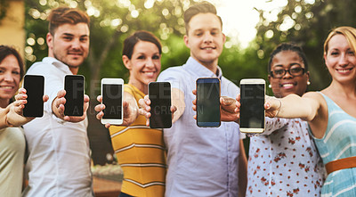 Buy stock photo Portrait of a group of cheerful young friends holding out their cellphones together and pointing it at the camera