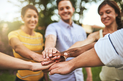 Buy stock photo Cropped shot of a group of cheerful young friends forming a huddle with their hands outside during the day