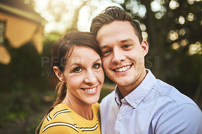 Buy stock photo Cropped shot of an affectionate young couple looking deep into each other's eyes while holding one another outside during the day