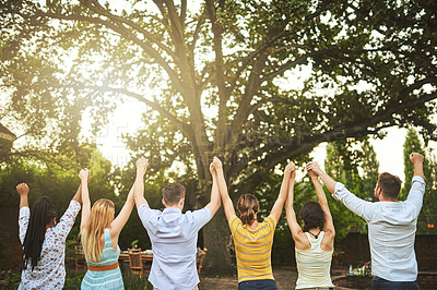 Buy stock photo Rearview shot of a group of young friends holding hands in the air outside during the day