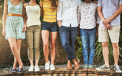Buy stock photo Shot of a group of unrecognizable friends standing  arms around outside during the day
