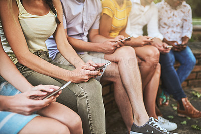 Buy stock photo Shot of a group of unrecognizable friends seated together while texting on their cellphones outside during the day