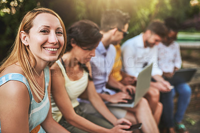 Buy stock photo Shot of a group of young friends seated together while texting on their cellphones outside during the day