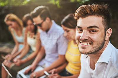 Buy stock photo Shot of a group of cheerful young friends seated together outside during the day