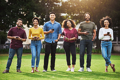 Buy stock photo Shot of a group of friends using their cellphones while standing together