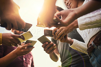 Buy stock photo Cropped shot of a group of unrecognizable friends using their cellphones
