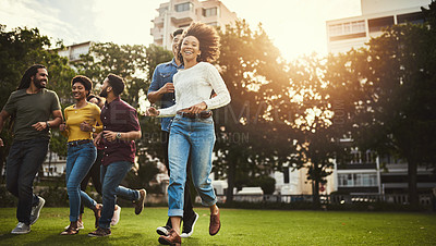 Buy stock photo Shot of a group of friends running outdoors
