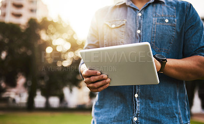Buy stock photo Cropped shot of an unrecognizable man using a digital tablet outdoors