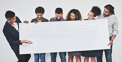 Buy stock photo Studio shot of a group of young businesspeople holding a blank sign against a gray background