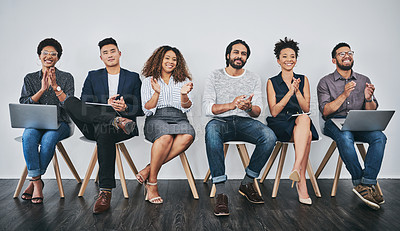 Buy stock photo Studio shot of a group of young businesspeople clapping while waiting in line against a gray background