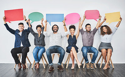 Buy stock photo Studio shot of a group of young businesspeople holding colorful speech bubbles in line against a grey background