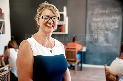 Buy stock photo Portrait of a confident middle aged teacher standing inside of her class while teaching her students