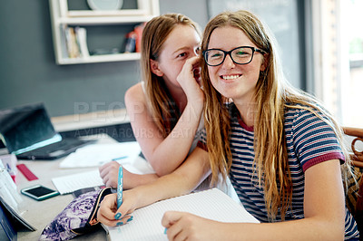 Buy stock photo Cropped shot of two young students doing schoolwork together while one whisper's in the other's ear