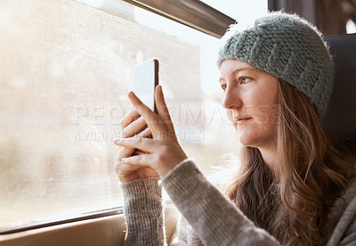 Buy stock photo Cropped shot of an attractive young woman taking photographs with her mobile phone while sitting on a train