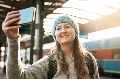 Buy stock photo Cropped shot of an attractive young woman taking photographs with her mobile phone while waiting for a train
