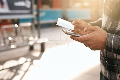 Buy stock photo Cropped shot of an unrecognizable young man sending text messages while waiting for a train