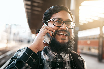 Buy stock photo Cropped shot of a handsome young man making a phonecall while waiting for a train