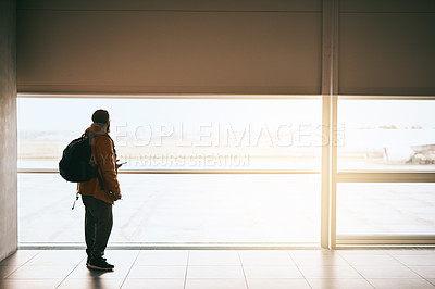 Buy stock photo Rearview shot of a young man looking out the window at an airport
