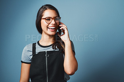 Buy stock photo Studio shot of an attractive young woman talking on a cellphone against a blue background