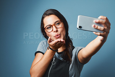 Buy stock photo Studio shot of an attractive young woman taking selfies against a blue background