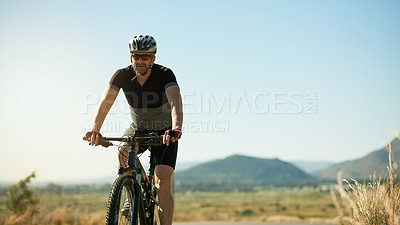 Buy stock photo Shot of a man riding a bicycle out in the countryside