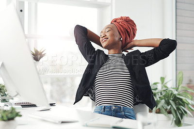 Buy stock photo Cropped shot of an attractive young businesswoman sitting at her desk with her hands behind her head