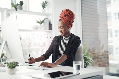 Buy stock photo Cropped shot of an attractive young businesswoman taking notes while working at her desk in the office