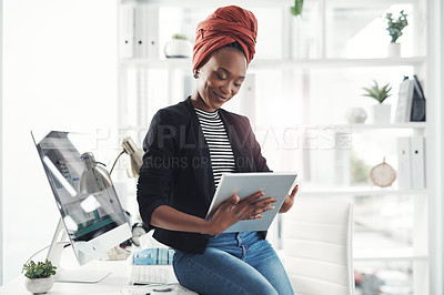 Buy stock photo Cropped shot of an attractive young businesswoman working on her digital tablet in the office